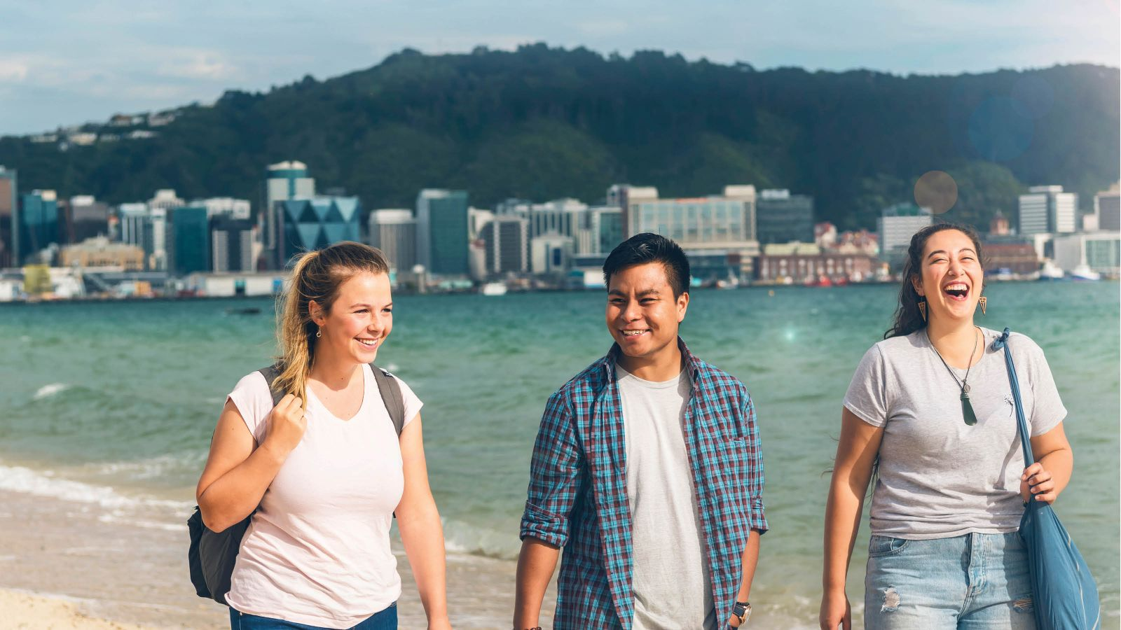 Three students smiling and walking along Oriental Bay Beach with Wellington city in the background.