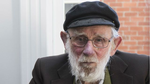 Arnold Heine in glasses and a black cap.