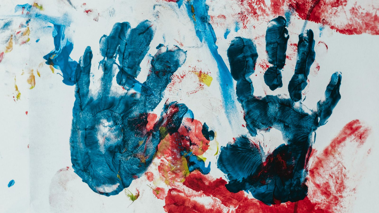 A child's finger painting with two blue handprints.