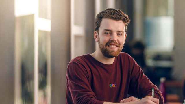 Smiling Commerce student, Fraser, is sitting at a table, holding a pen, in Rutherford House on the Pipitea campus.