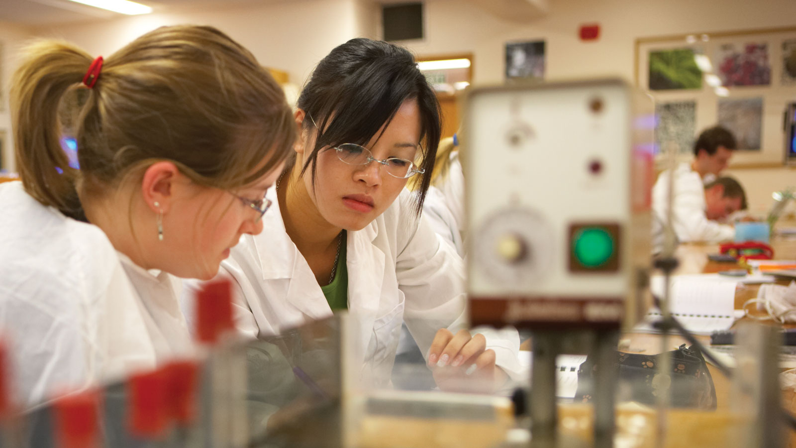 Two female students are working together in a lab, and wear white lab coats.