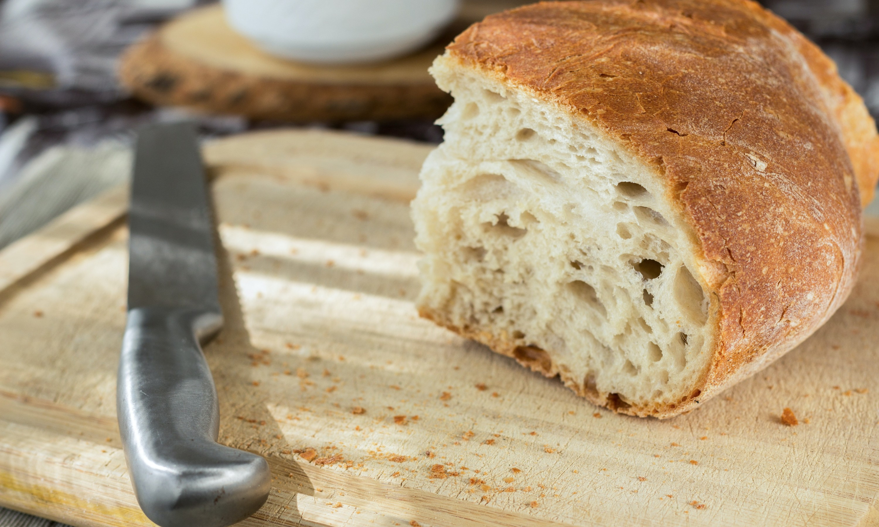 A loaf of bread on a chopping board with a bread knife.