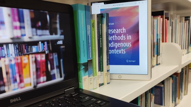 Multicoloured spines of selection of  print books on a library shelf with a black laptop displaying eBooks, and a white tablet, displaying the front cover of an eBook, emerging from between the print books.