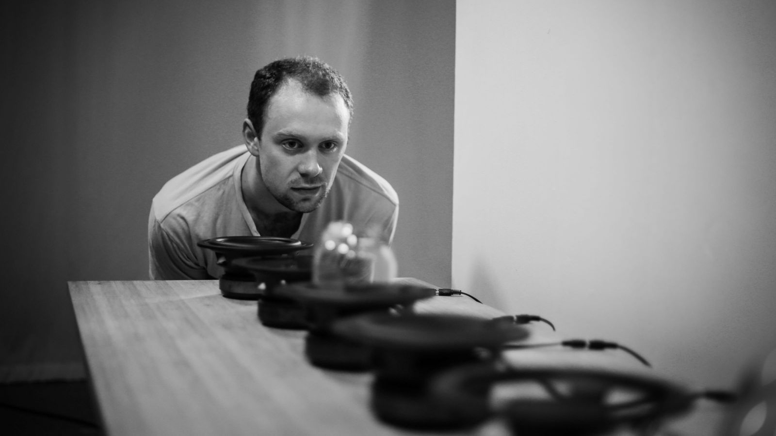 A man leans down to a table with round black indistinguishable obects lined up. The photo is in black and white.