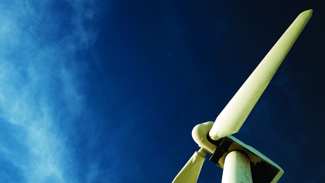 Upper portion of an electricity-generating windmill against a blue sky.