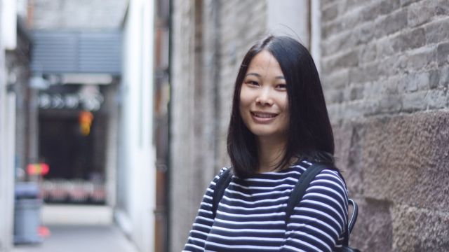 A young Chinese woman in a stripy top stands outside in front of a grey building.