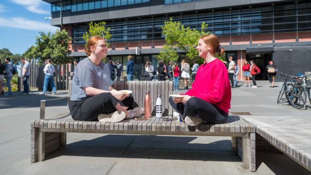 Two students sitting cross-legged on a bench facing each other and talking.