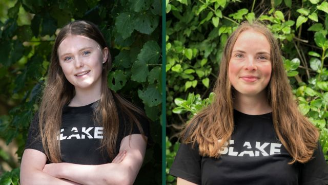 Elizabeth Werner and Brittany Florence-Bennett stand in front of green bush wearing their black Blake Ambassador t-shirts.