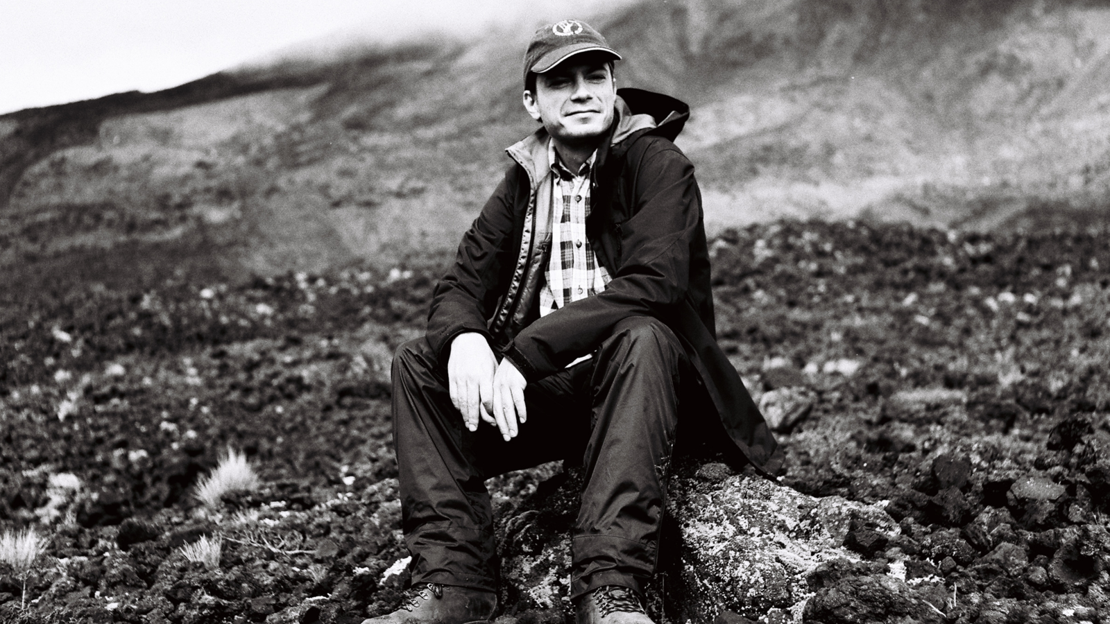 A black and white image of Finnigan sitting on a hill wearing outdoor weather gear.