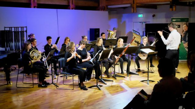 Wide shot of large ensemble with conductor