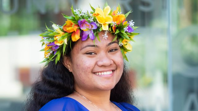 Smiling girl with brown skin wearing flower headdress