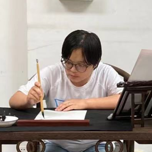 Asian person with glasses holds a calligraphy pen