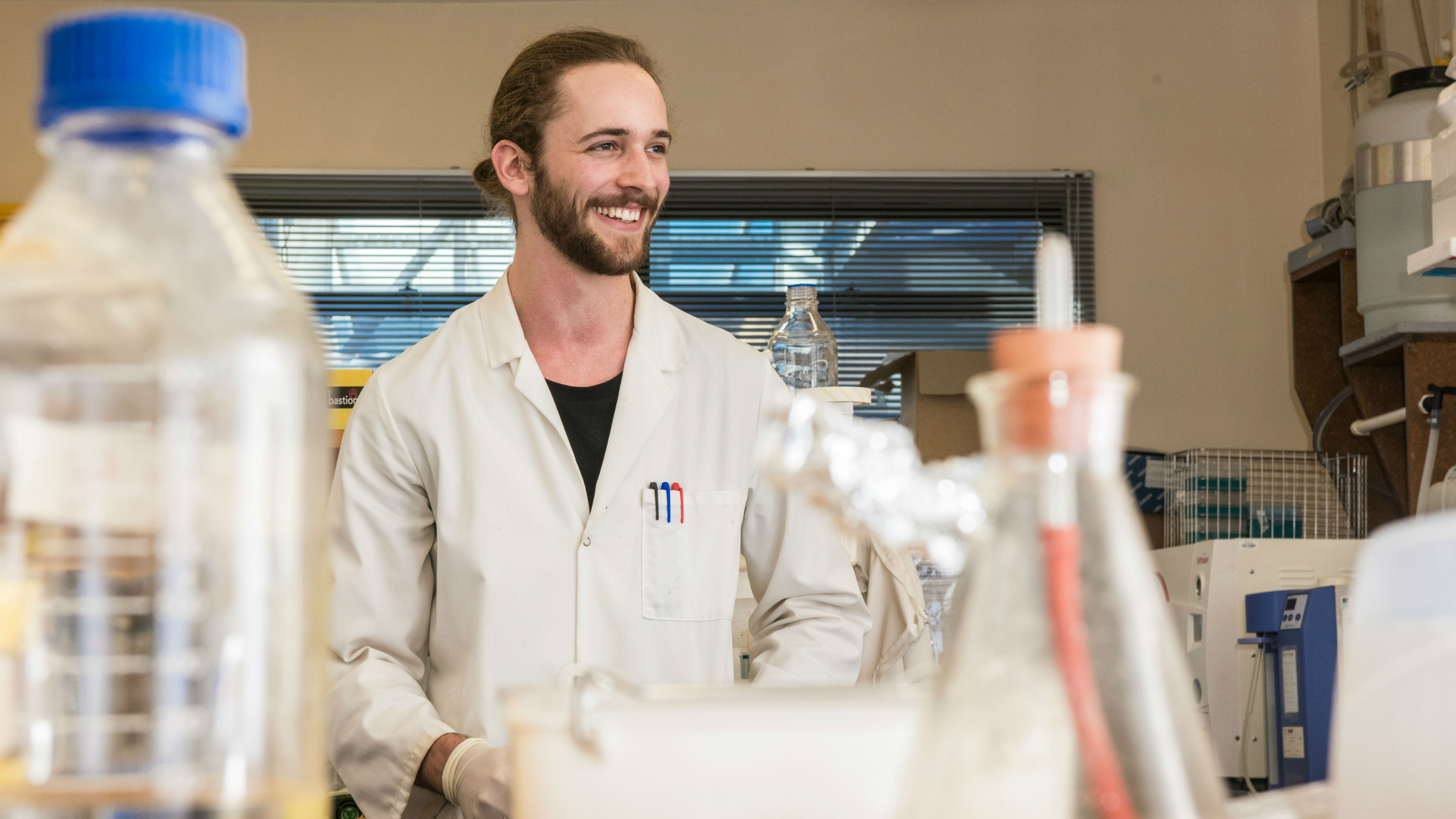 A student wearing a white lab coat stands smiling over science eqiupment in a laboratory.