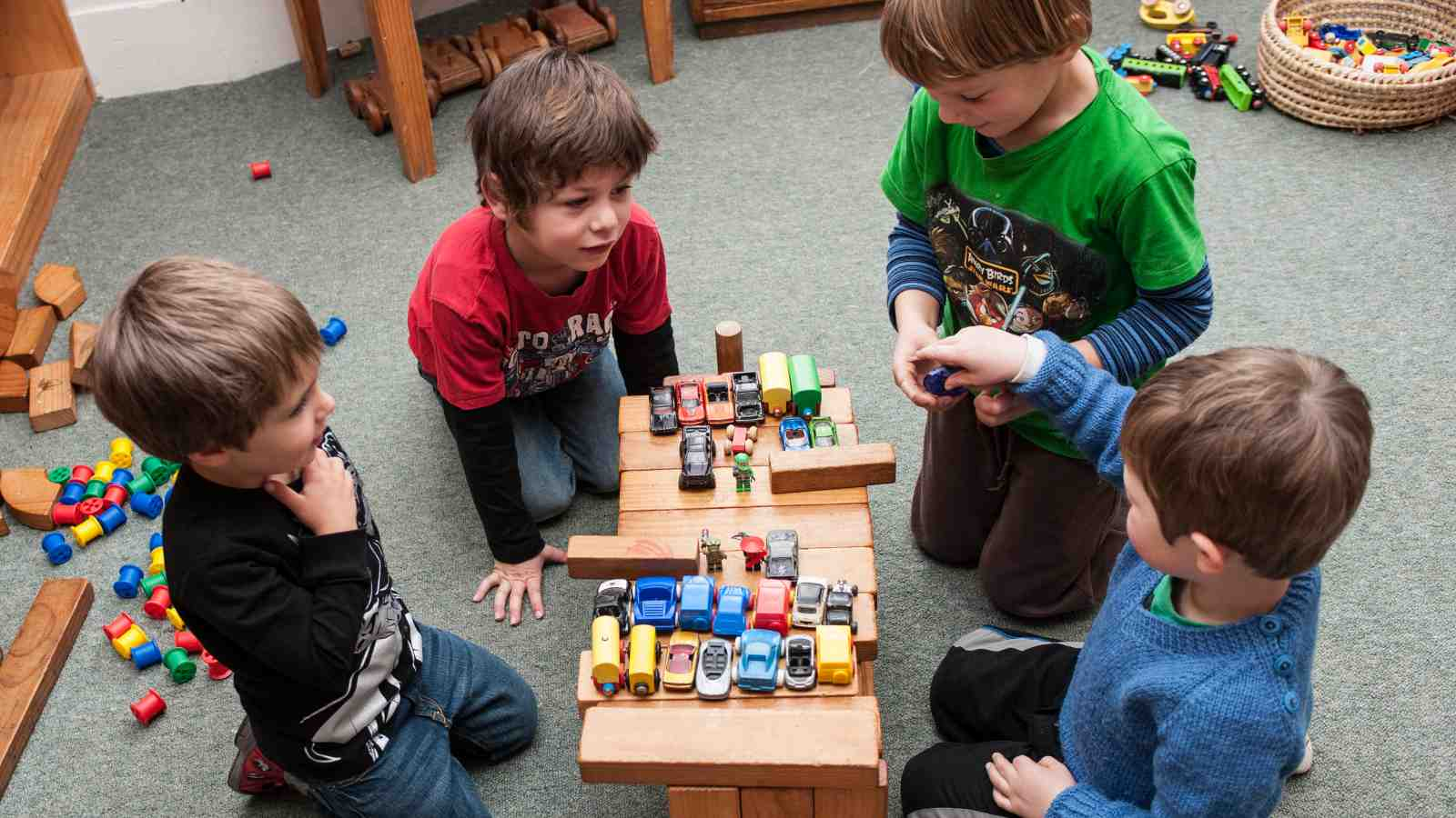 Four young boys play with blocks and toy cars together.