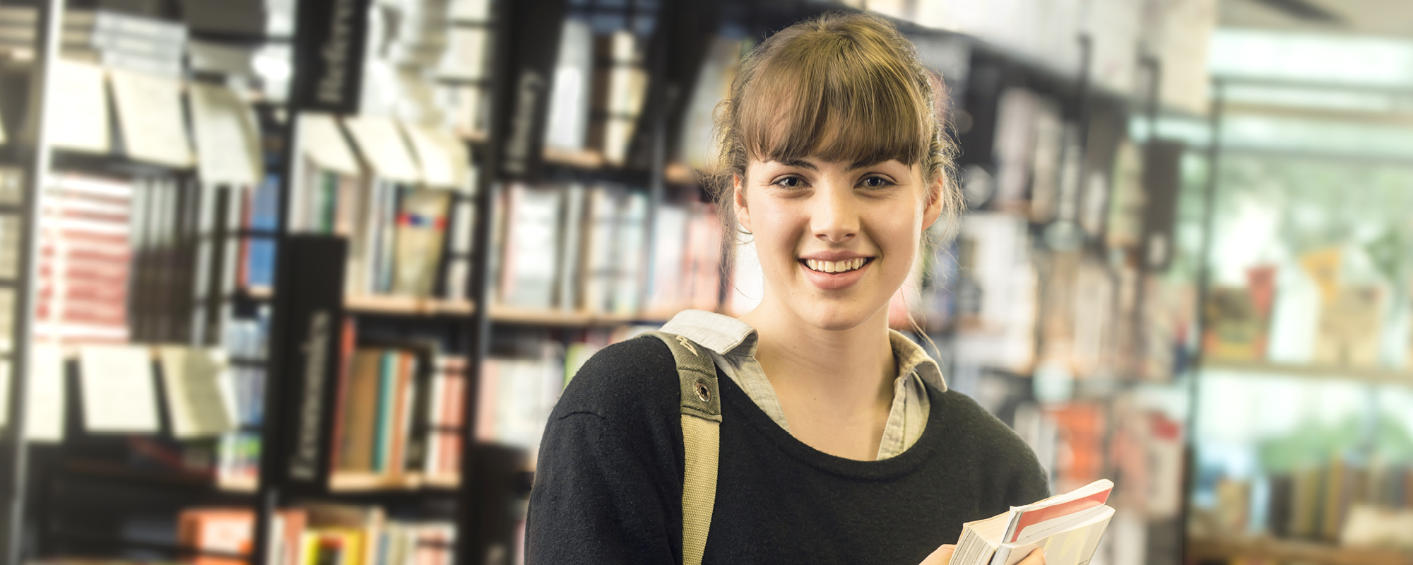 A smiling female student holds a book in front of a bookshelf.