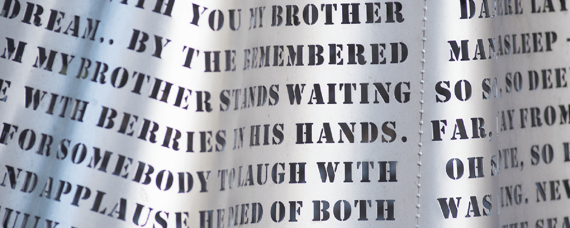 An image of a stainless steel sculpture with many sentances mad up of letters that have been cut out of the steel.