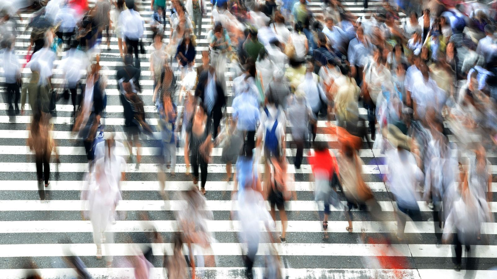 A blurred image of people crossing the road.