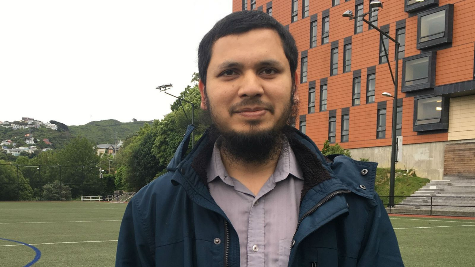 Arif stands in the middle of a sports field, with rolling hills and an orange building behind him.