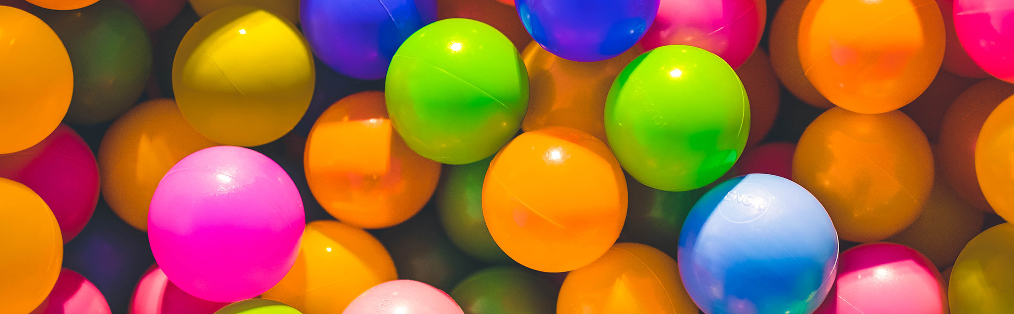 Banner image – colourful toy balls, the kind that would be in a ball pit for kids to play in.
