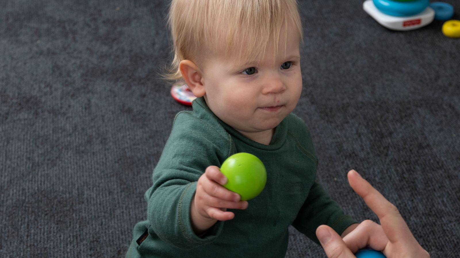 A child passes a green toy ball to an instructor.