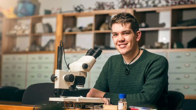Smiling Science student, Theo, is sitting at a desk with a microscope in front of him in a laboratory in Te Toki a Rata on Kelburn campus.
