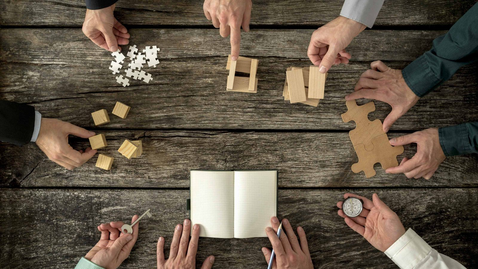 An image of hands around a wooden table holding various small objects, like a compass, small cubes, puzzle pieces, a key and a note book.