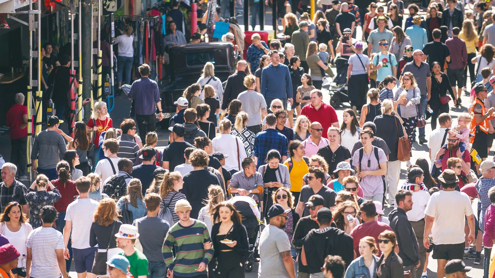 A bird's-eye view of a crowd of people at a street festival on a sunny day.
