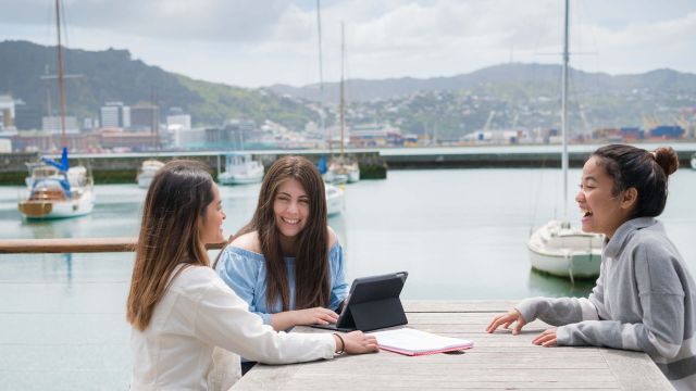 Three students by harbour with books and tablet undertaking groupwork.