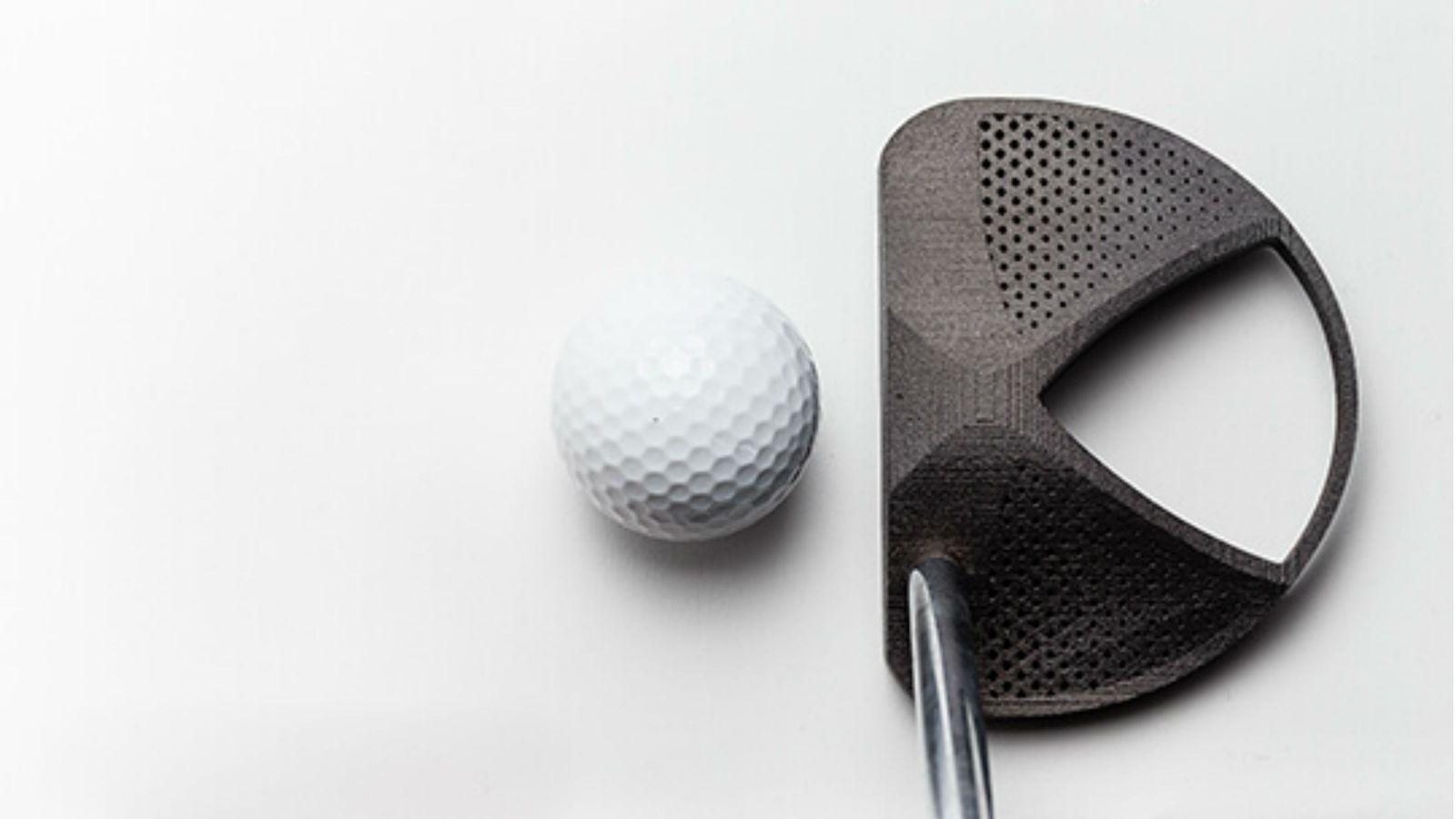 A photograph of the top of a golf ball and club.