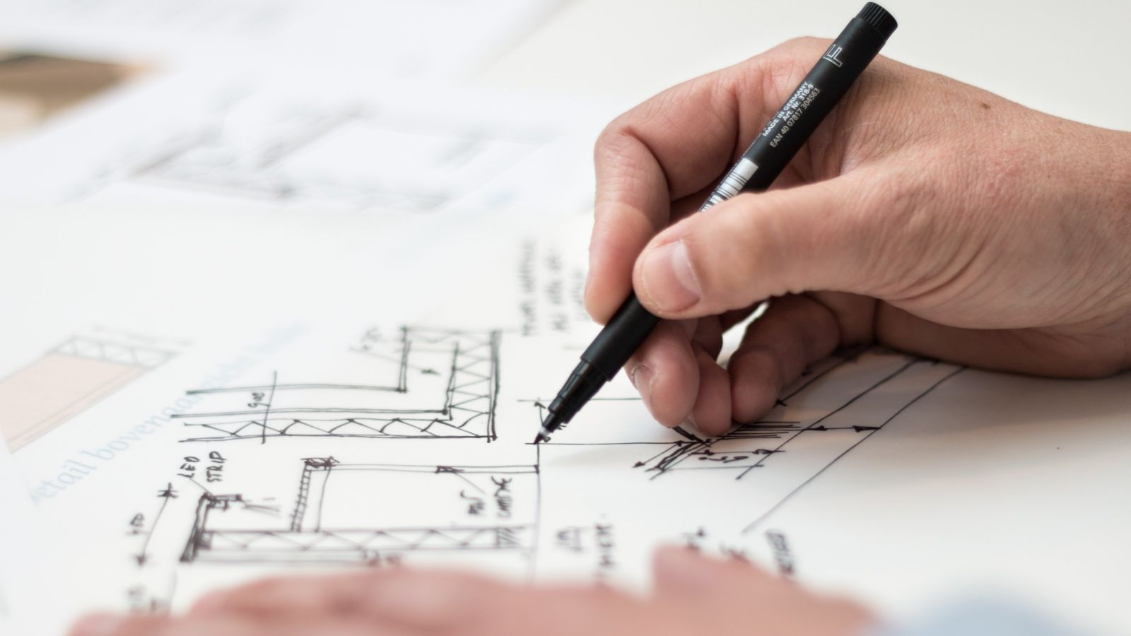 person holding black pen drawing architectural plans