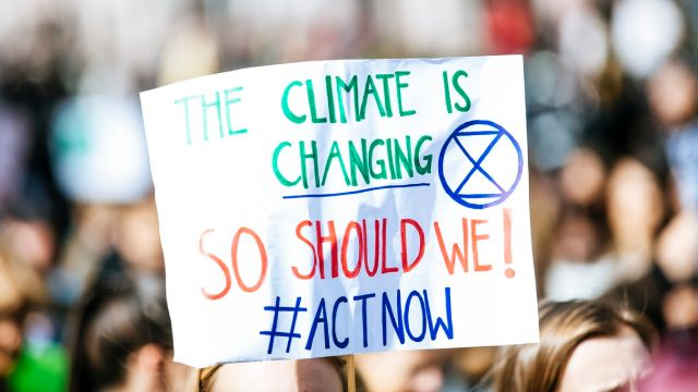 A protestor holds a sign that reads, the climate is changing so should we, #actnow.