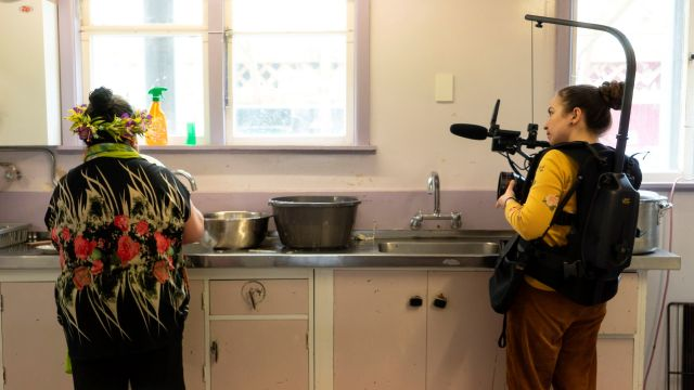 A person with a body camera films another in a kitchen