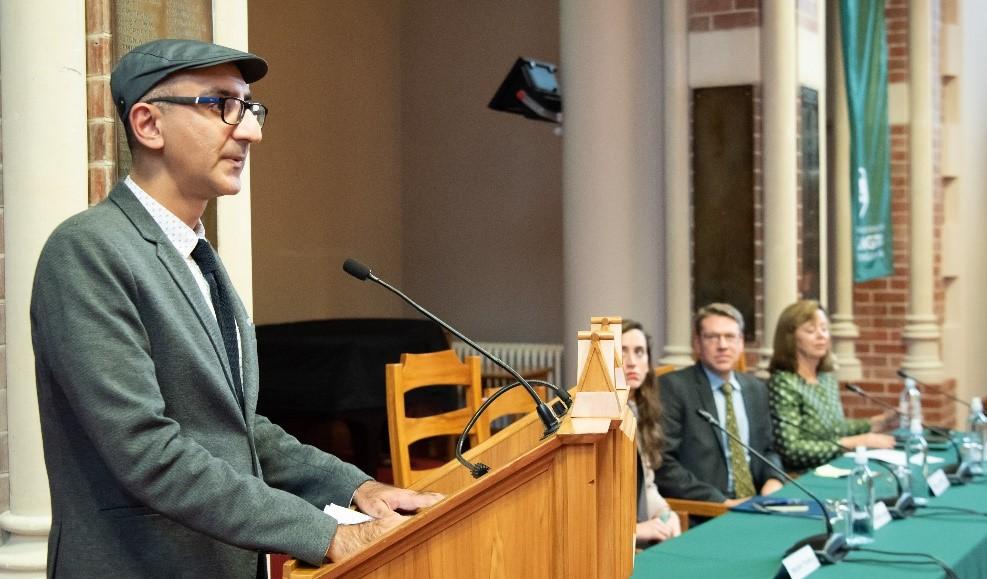 Manjeet speaks at a lectern.