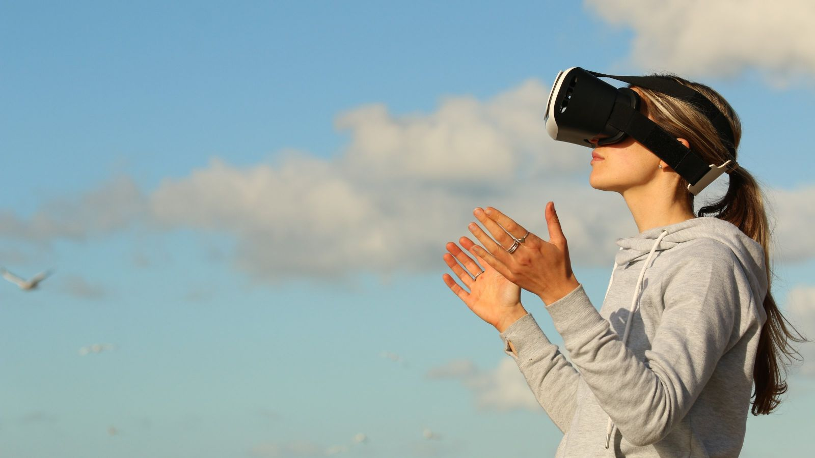 Woman wearing VR headset in front of sky with clouds