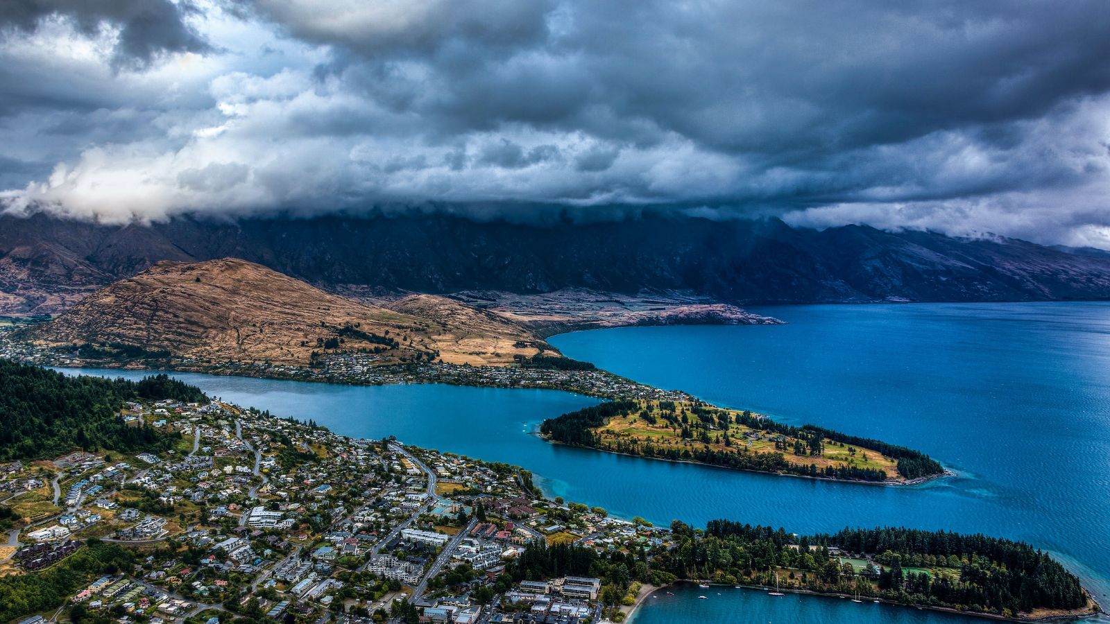 Queenstown from aeroplane view - water, hills and city with dark clouds in the sky