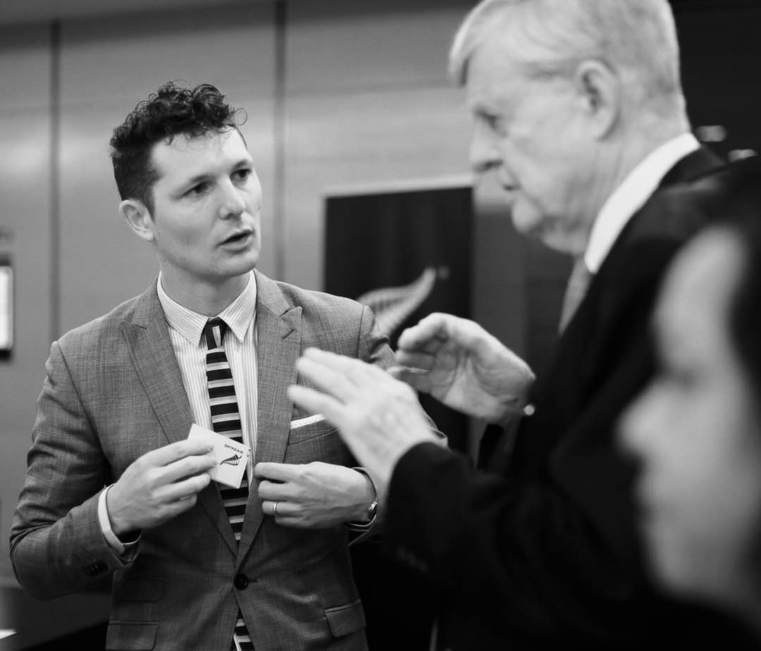 Adam McCnnochie speaking to a guest at a function.
