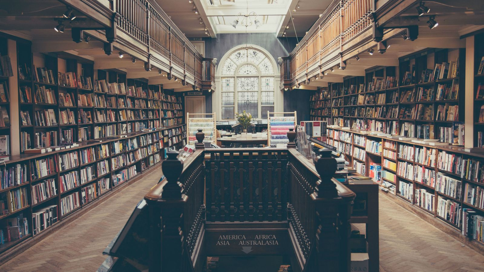 A grand old library with a staircase and an etched arch window.