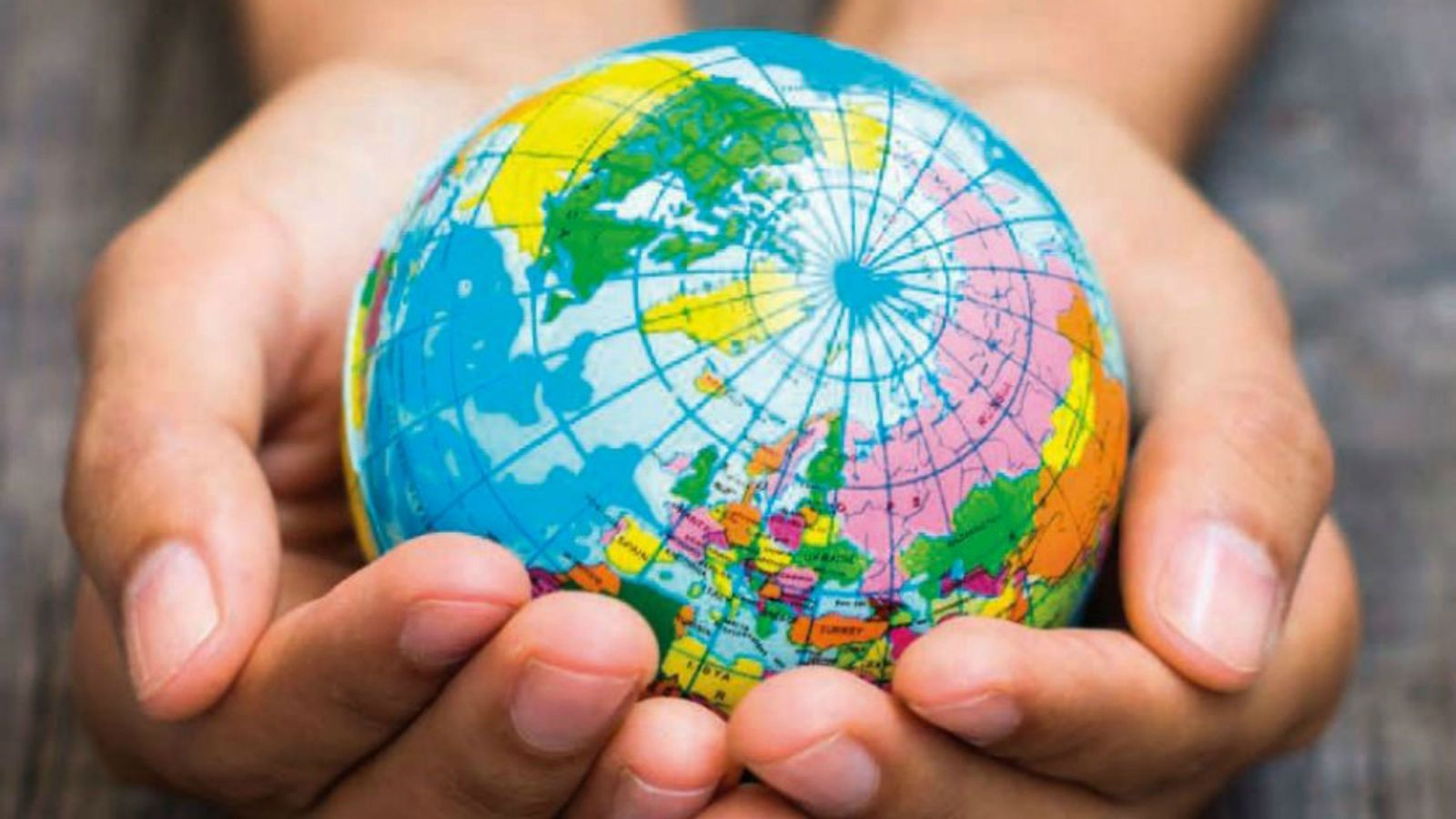 A small, colourful globe sitting in two hands.