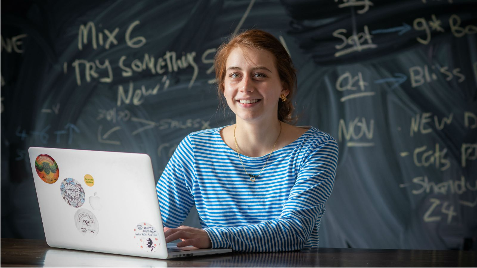 Clea Molano sits at a table with a laptop in front of her and a blackboard with white chalk writing behind her.