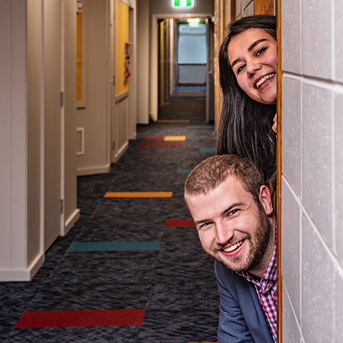 James Lynezx and Kyndra Garton peeking their heads around the door of a room at Victoria House
