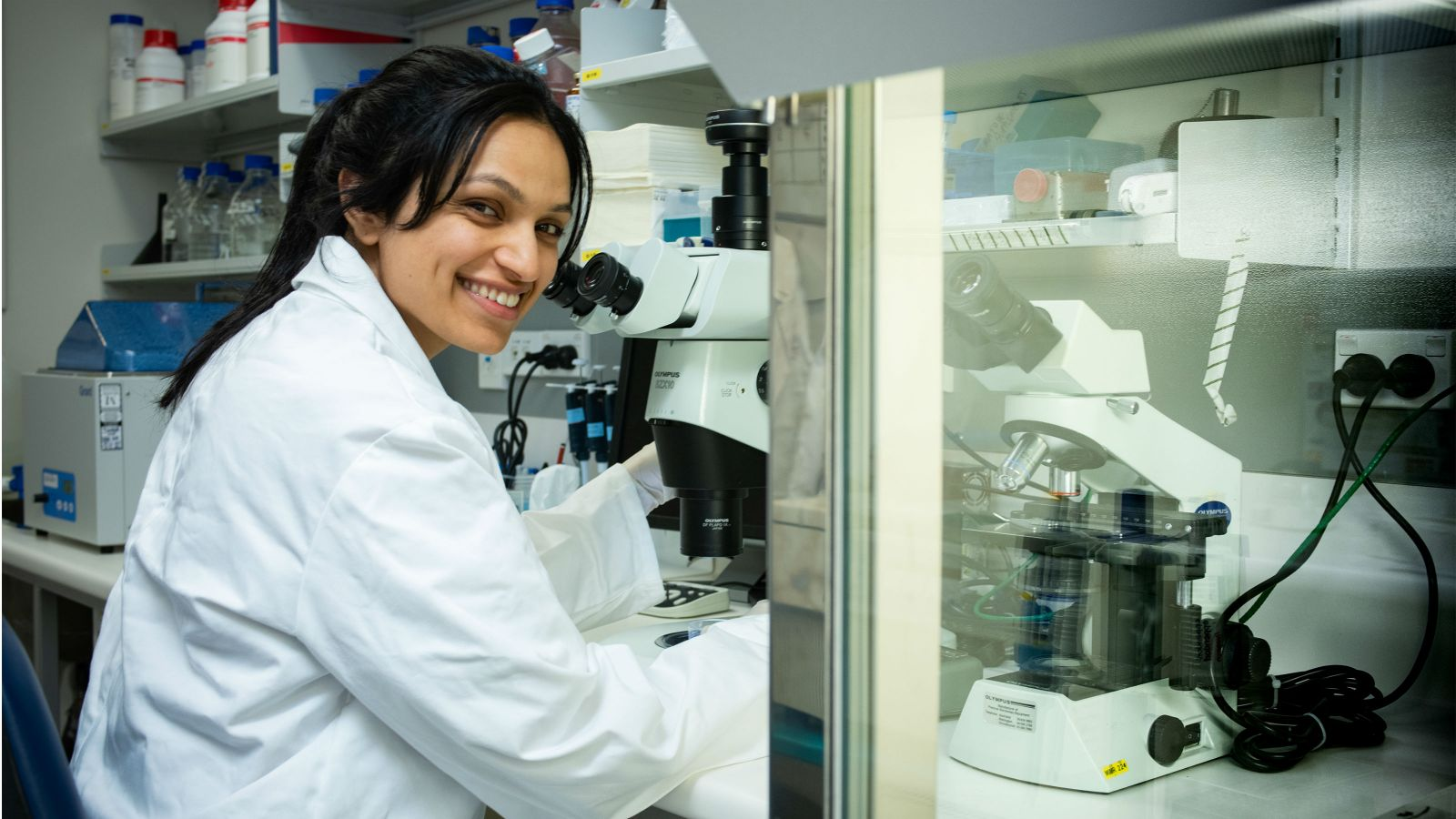 Palak, wearing a white lab coat, sits by a microscope.