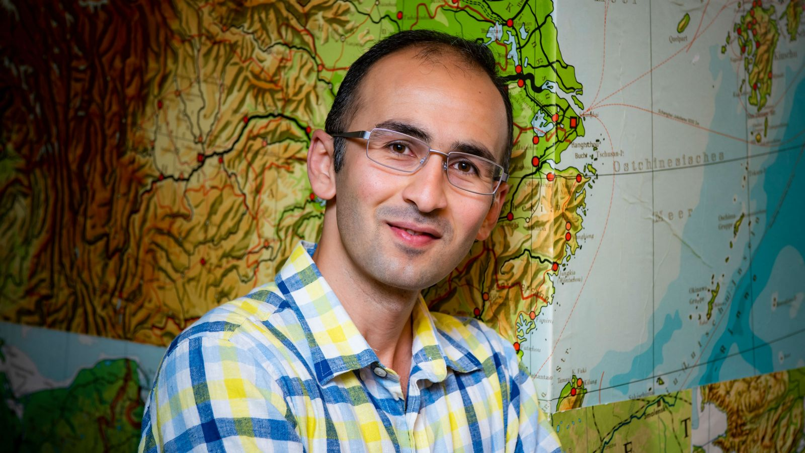 Omid leans against the wall and looks at the camera. The wall paper is a world map.