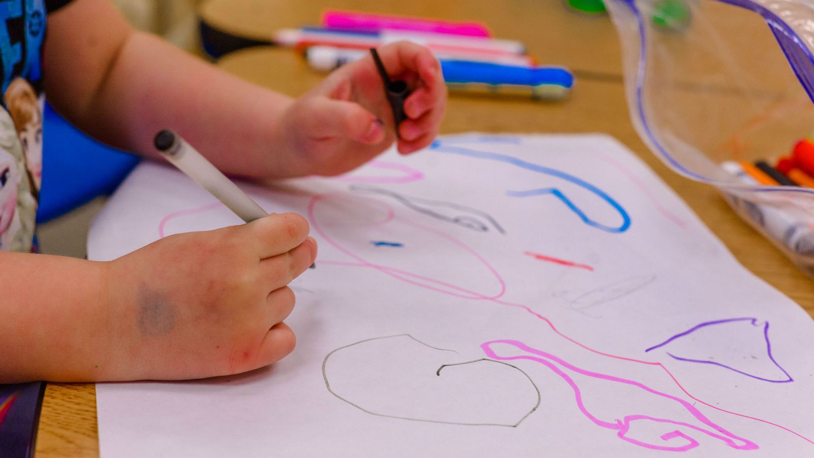 A child draws squiggly lines with a marker on paper.