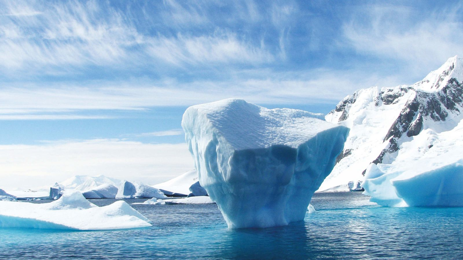 A large iceberg sticking out of the ocean.
