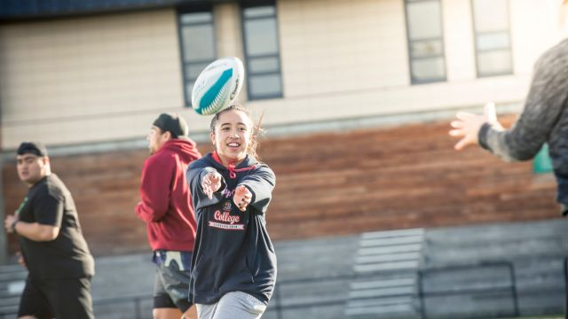 Action shot of female student throwing rugby ball.