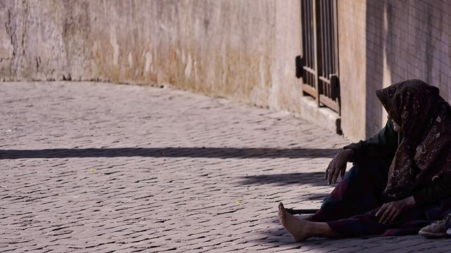 A man sits on the street with no shoes on.