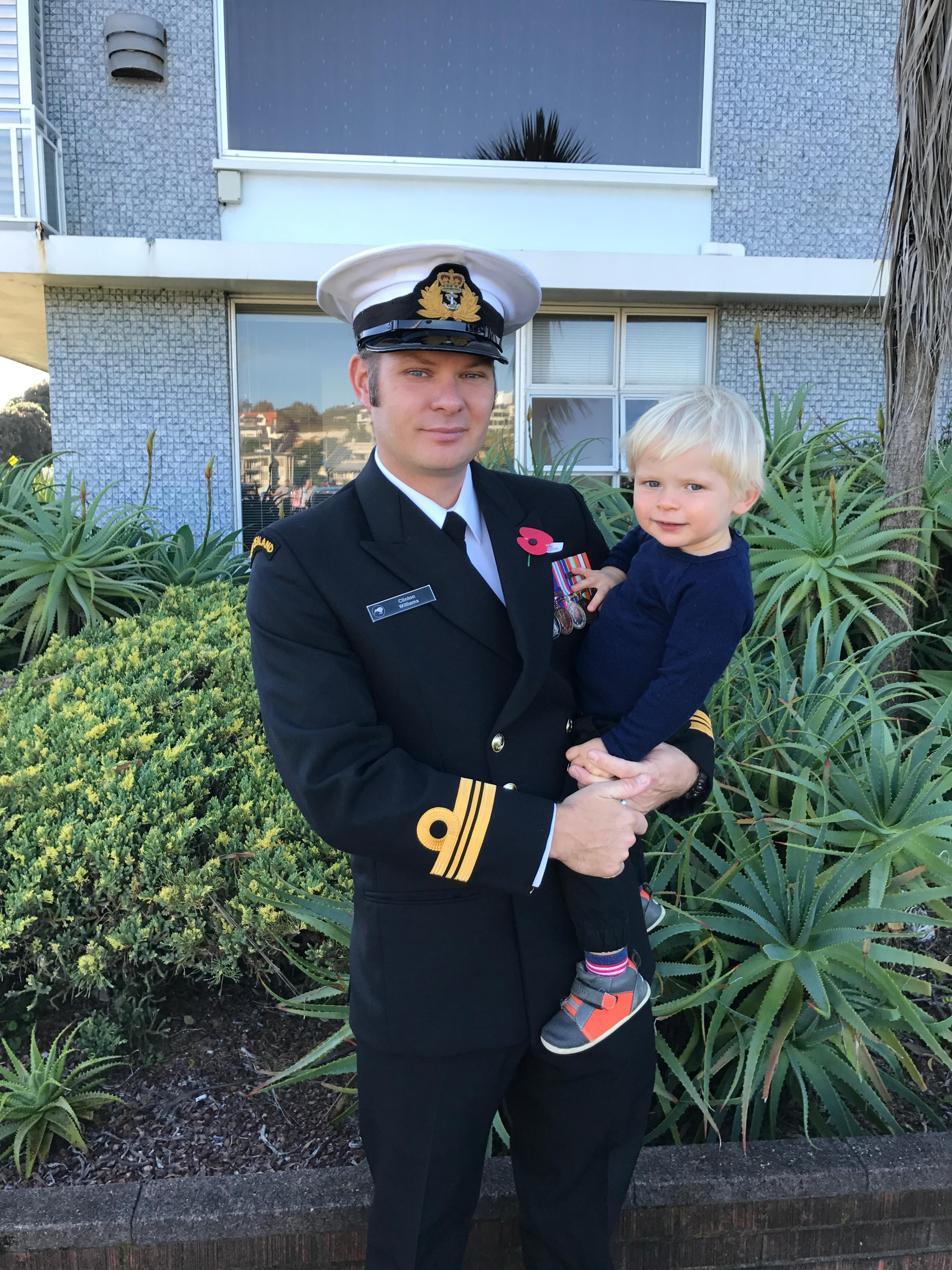 Clinton Williams in uniform on ANZAC day, carrying his child