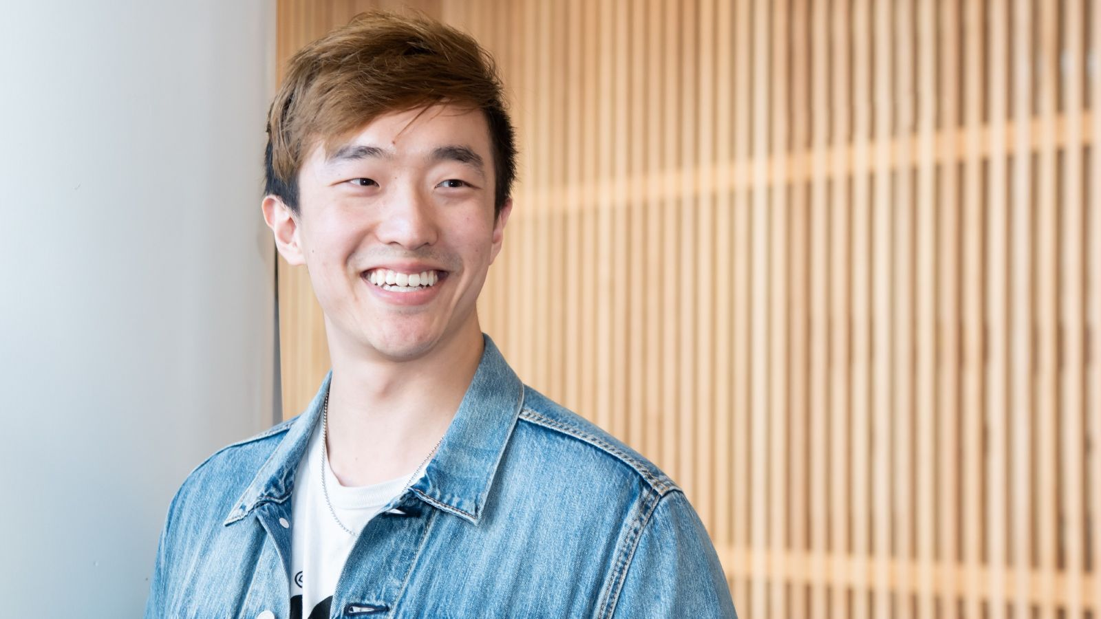 Oliver Ruan smiling in front of wood panel background