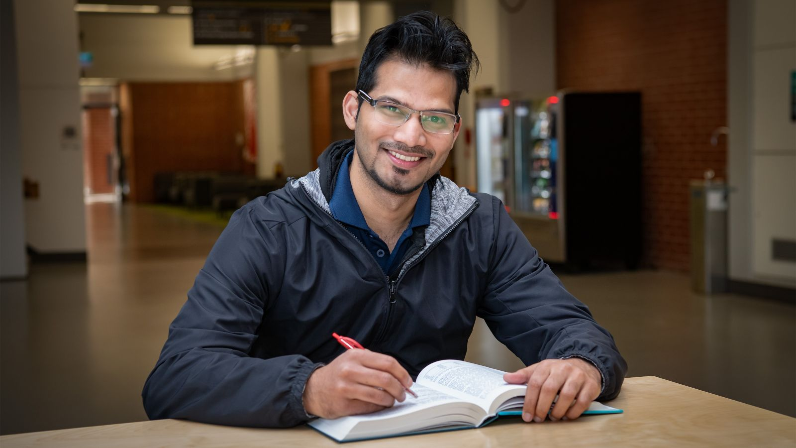 Akib Mohammad smiles at the camera while working with a book