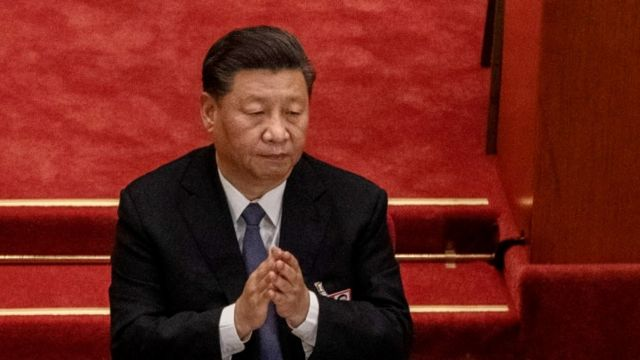 Xi Jinping clapping with red background.